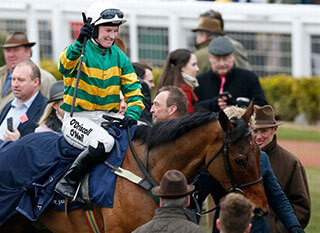 Jockey in the middle of a small crowd at Cheltenham
