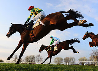 Jockeys jumping over the fences during Novices' Handicap Chase at Cheltenham Festival