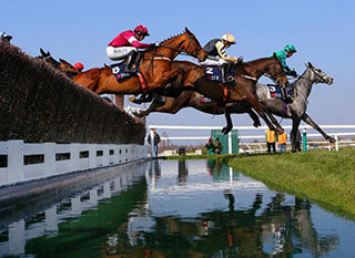 Stunning image of horses jumping a fence during the JLT Novices' Chase