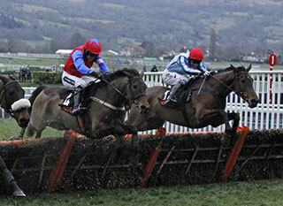 Three horses jumping the fences at the Randox Health County Handicap Hurdle